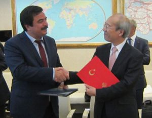 Mr. Yuichi Yamaura, Vice President of the Japan Aerospace Exploration Agency (right), and H.E. Dr. Cihan Kanlıgöz, Director General of the Aeronautics and Space Technologies, the Ministry of Transport, Maritime Affairs and Communications of the Republic of Turkey (left), exchange copies of the Cooperative Agreement in Ankara, Turkey, on 8 September 2016.